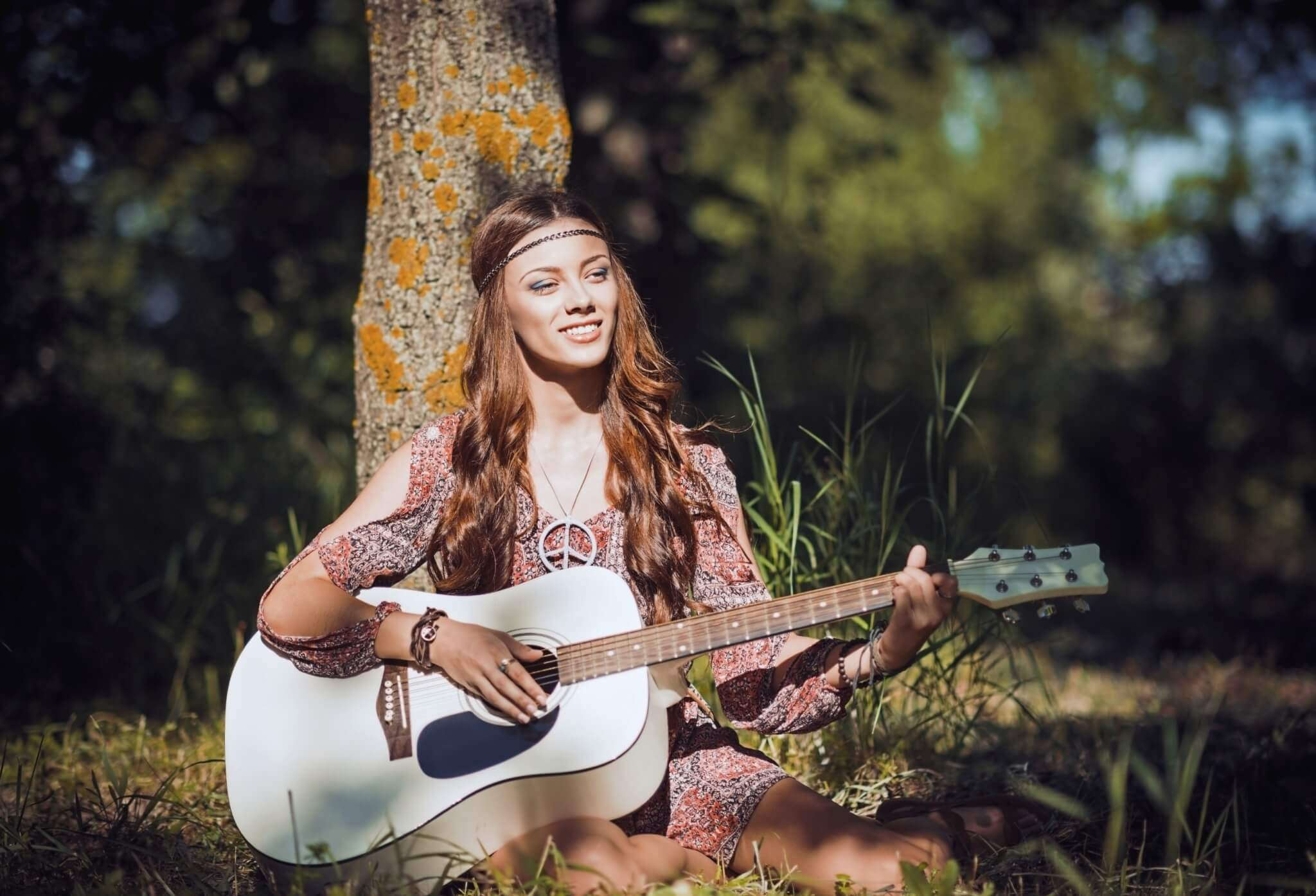 Beautiful-young-hippie-girl-sitting-under-tree-and-playing-guitar-000084782947_Large.jpg.jpeg