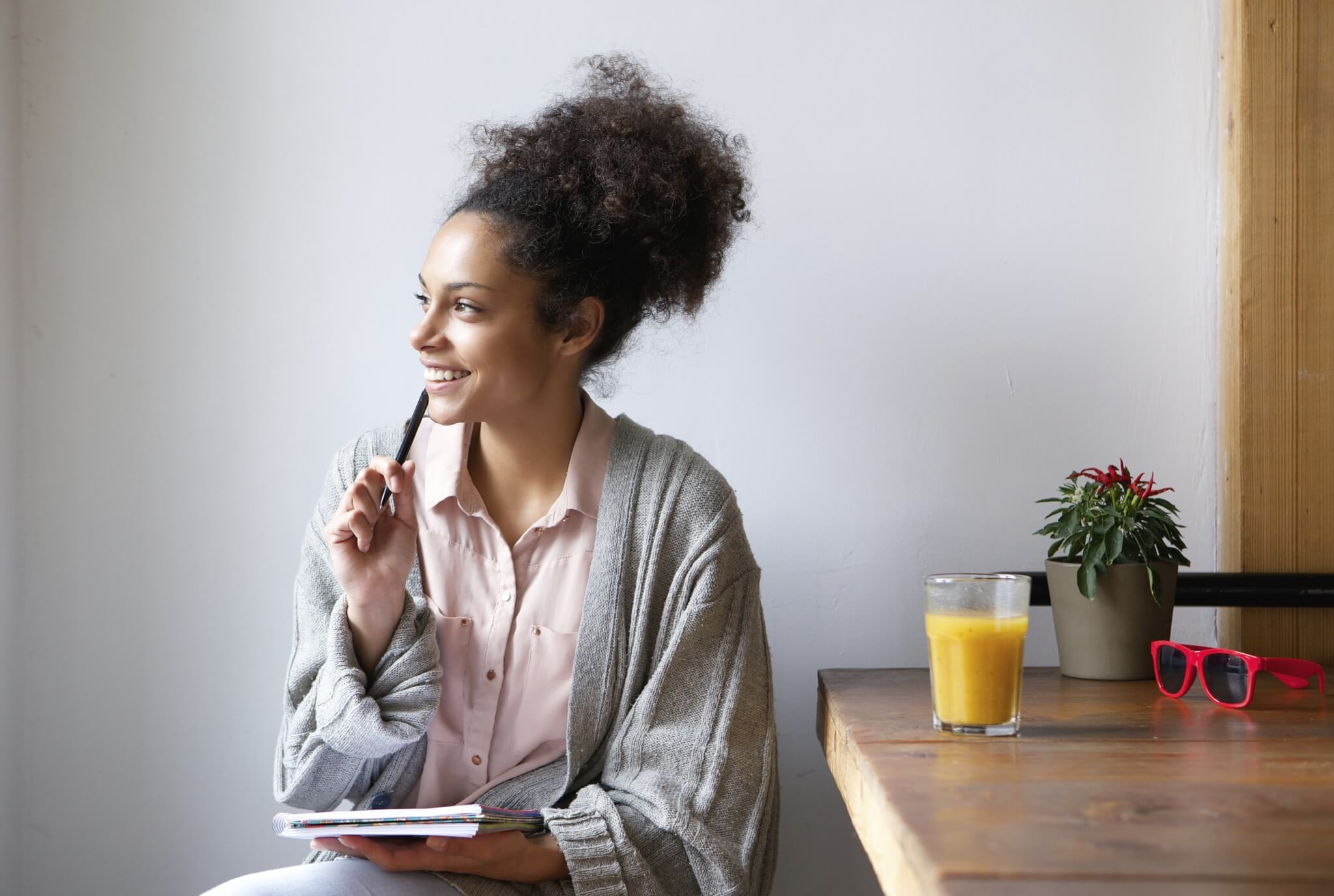 Happy-young-woman-sitting-at-home-with-pen-and-paper-000067132741_Large.jpg