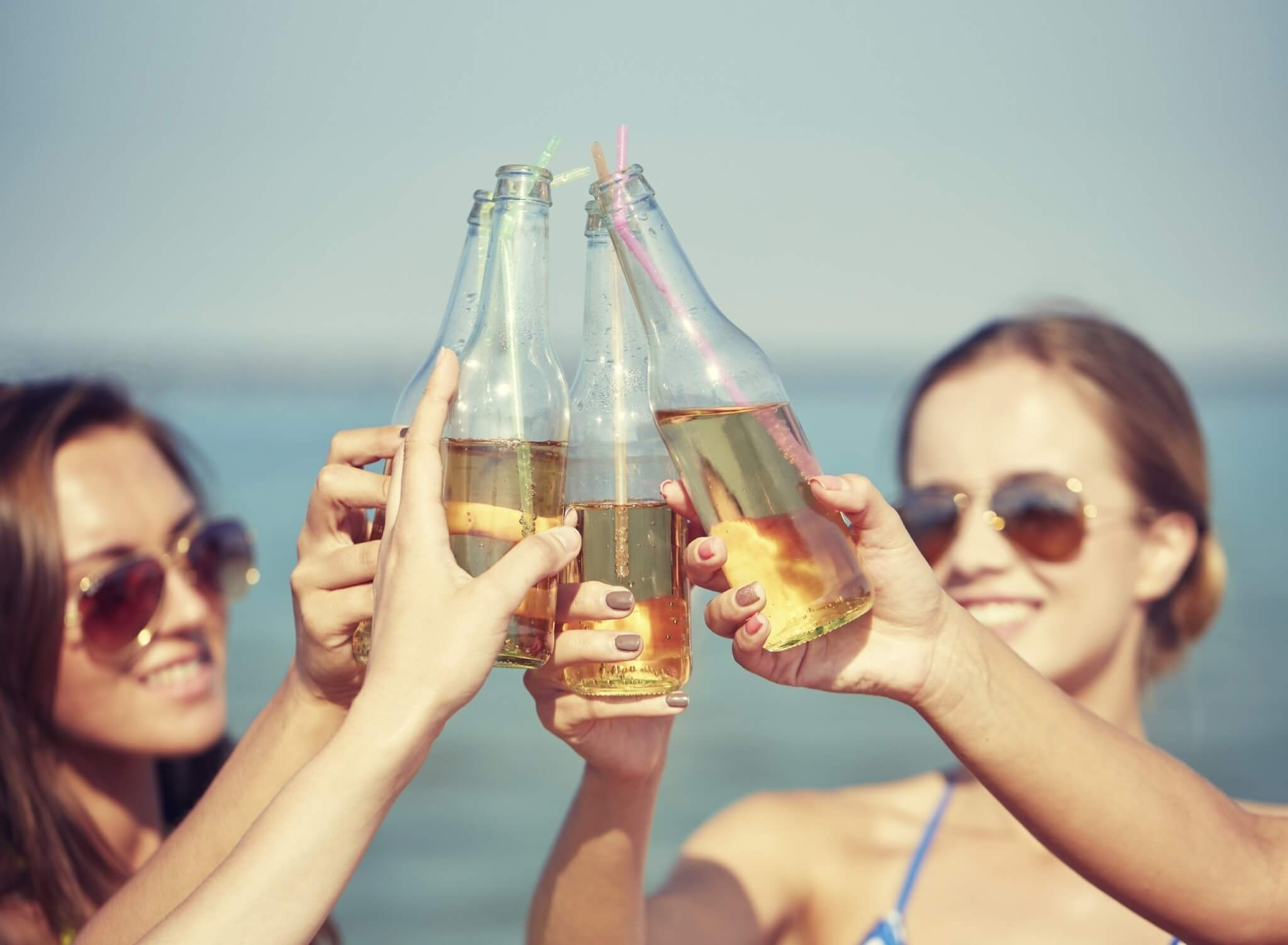 close-up-of-happy-young-women-with-drinks-on-beach-000069864029_Large-2.jpg.jpeg